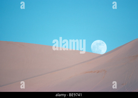 Full moon rising above sand dunes - Stock Image