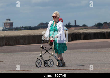 An elderly lady walking with a Zimmer frame or mobility aid - Stock Image