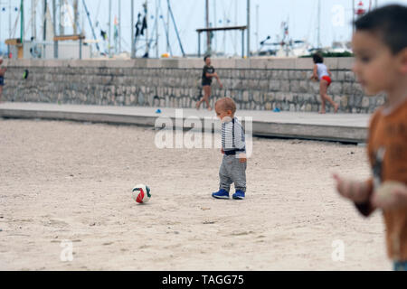 Baby Boy is Playing With a Soccer Ball on Sand on Sea Beach - Stock Image