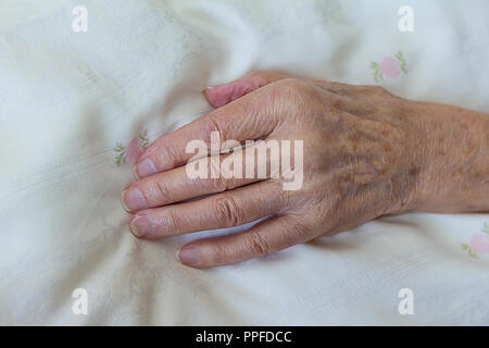 One gaunt hand of an old woman with a terminal illness like cancer on a light duvet cover, concept of death, dying - Stock Image