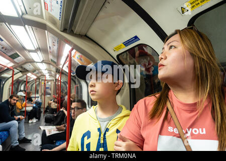 A mother and son ride a London Underground train on a day trip to London. - Stock Image