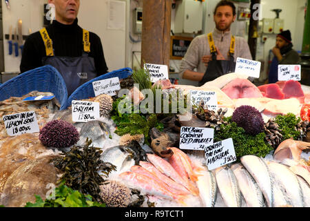 Fishmongers selling various fresh fish on Borough Market seafood stall in November Southwark South London England UK  KATHY DEWITT - Stock Image