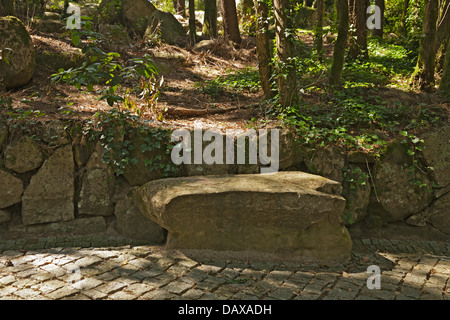 Sintra Gardens, Pena stone garden seat in the woods - Stock Image