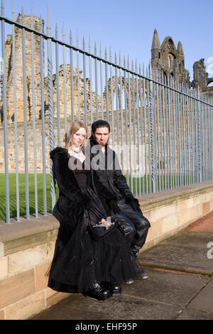 Couple by the ruins at Whitby Goth Weekender. - Stock Image