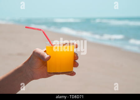 closeup of a young caucasian man on the beach, with a glass with a refreshing orange drink in his hand, with the sea in the background - Stock Image
