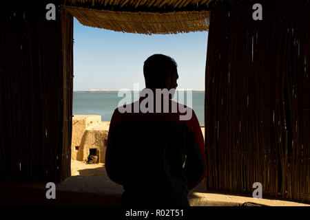 Sad man looking in window and thinking. Siwa. Egypt - Stock Image
