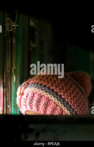 A woman wearing a pink knitted wooly hat looks out the window of a train. - Stock Image