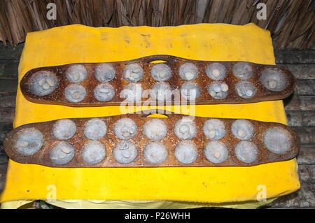 Betel nut grinding bowls set out at the Bajau (sea gypsy) tribal house at Mari Mari Cultural Village, Kota Kinabalu, Sabah, Malaysian Borneo - Stock Image