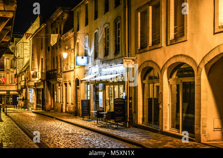 An empty picturesque cobblestone street with half timbered buildings, shops and sidewalk cafe late at night in the - Stock Image