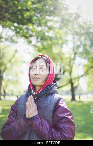Serene active senior woman meditating in sunny park - Stock Image