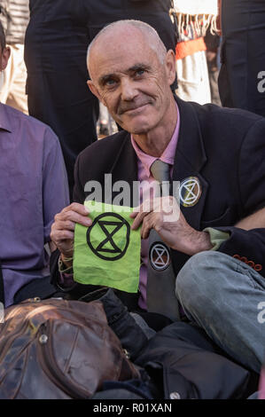 LLondon, UK. 31st October 2018.  Most people at Extinction Rebellion's Declaration of Rebellion left the road they were blocking in front of parliament after a closing address by George Monbiot, but several small groups decided to remain on the road, including Donnachadh McCarthy and George Monbiot. Police immediately warned them they would be arrested if they did not move, and by the time I left around 15 arrests had been made, including of McCarthy, while some others agreed to leave the road. Peter Marshall/Alamy Live News - Stock Image