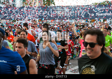 Woman amidst throng of runners crowding together at starting line of 2014 Mercedes-Benz Corporate Run in Miami, Florida, USA. - Stock Image