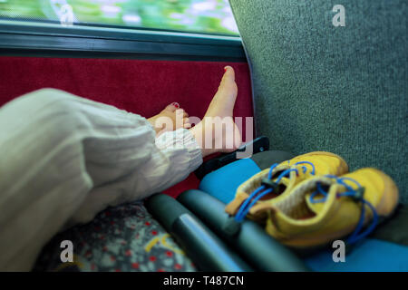 Feet of a yound child who is relaxing in a bus after a long day - Stock Image