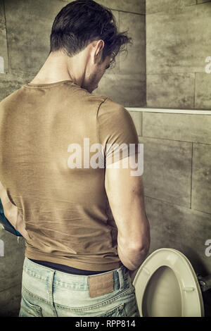 Rear View of a Young Man Peeing at the Toilet - Stock Image