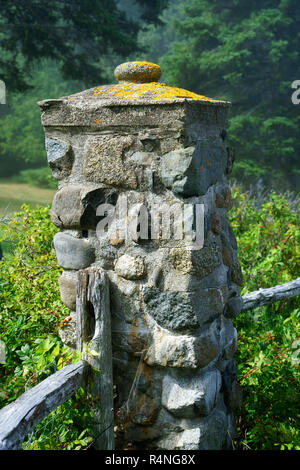 Weathered stone pillar, part of an old fence bordering the Shore Path in Bar Harbor, Maine, USA. - Stock Image