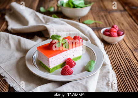 Sweet spinach cake with raspberry mousse and layer of jelly, decorated with fresh mint - Stock Image
