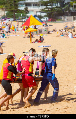 A near drowning victim carried off Palm beach on a stretcher by surf rescue volunteers and ambulance paramedics,Sydney,Australia - Stock Image