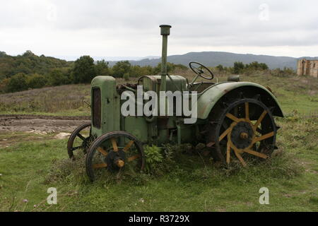 A shot of an old tracktor on a field - Stock Image