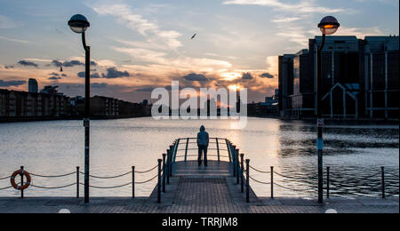 The silhouette of a young man in a hoody looking away from the camera at a dock in London's Docklands. - Stock Image