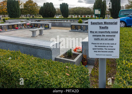 Sanctum Memorial Vaults in the garden of Remembrance in Acklam cemetery Middlesborough with a notice requesting people not to sit on them - Stock Image