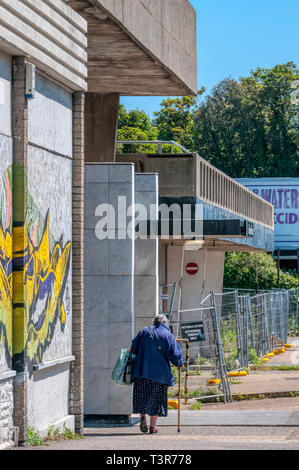 An elderly woman with a walking stick in a harsh urban environment - Stock Image