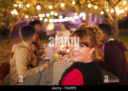 Portrait happy woman enjoying dinner garden party - Stock Image