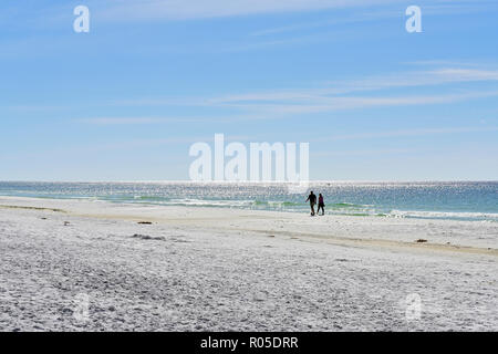 People walking along secluded and empty Florida panhandle beach at Deer Lake State Park, Florida USA. - Stock Image