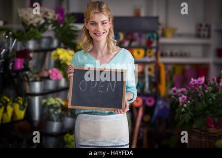 Smiling female florist holding open sign on slate in flower shop - Stock Image
