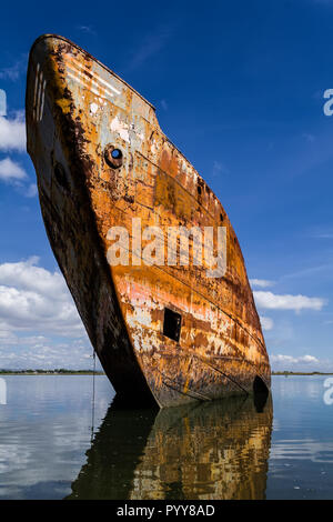 Old rusty ship run aground or beached, rusting on the shore. Salvage of scrap metal to recycle on the shipyard recycling industry. Seixal, Portugal - Stock Image