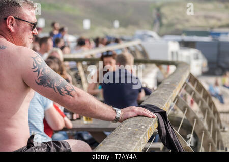 The tattooed arm of a holidaymaker on a balcony at Fistral in Newquay in Cornwall. - Stock Image