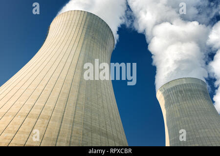 power plant cooling towers steaming on dark blue sky background - Stock Image