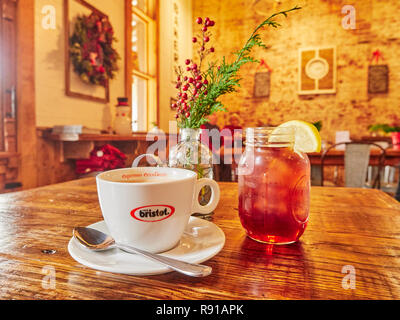 Bristot espresso eccellente coffee cup and glass of sweet iced tea with lemon sit on a restaurant table in the Lightnin' Bugs Cafe in Warm Springs GA. - Stock Image