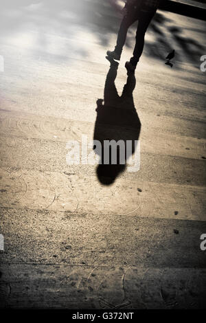 Sihouettes and shadow of aman crossing the street - Stock Image