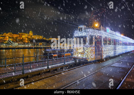Budapest, Hungary - Festively decorated light tram (fenyvillamos) on the move with Buda Castle Royal Palace at Vigado square on a snowy night - Stock Image
