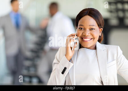 beautiful young African entrepreneur talking on cell phone - Stock Image