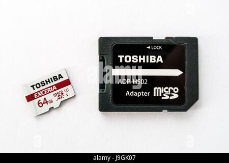 Toshiba Exceria microSD XC memory card with a capacity of 64GB, and a microSD to SD card adapter on white background. - Stock Image