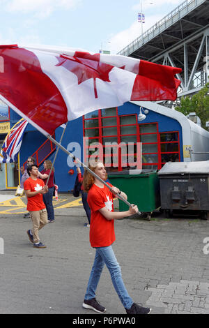 Vancouver, Canada.1st July, 2018. A young man waves the Canadian flag  in the annual Canada Day Parade on Granville Island, Vancouver, British Columbia. This year Canada Day celebrates the country's 151st birthday. Credit: John Mitchell/Alamy Live News - Stock Image