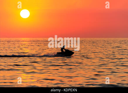 Jetski is a sunset silhouette of a waverunner jetski male riding along the ocean water at sunset. - Stock Image