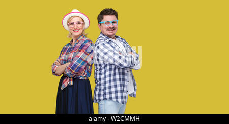 Couple of friends, adult man and woman in casual checkered shirt standing together back to back with crossed arms, toothy smile, looking at camera. In - Stock Image