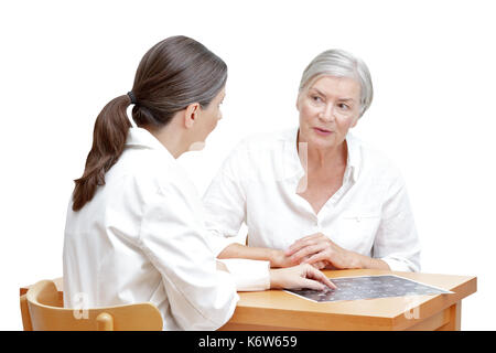 Female middle aged doctor showing her senior patient an ct scan of her head, isolated on white background - Stock Image