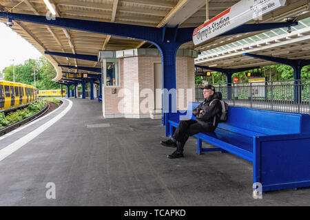 U-Bahn Olympia-Stadion underground railway station on U 2 line in Westend district, Berlin. Elderly man waiting for train on platform. The station Sta - Stock Image