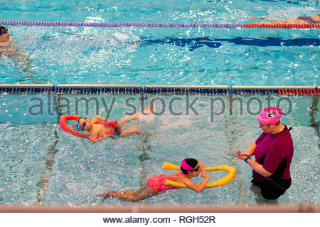 Poznan, Poland - January 26, 2019: Children swimming with sticks and instructor during swim lessons at a pool in the Termy Maltanskie. - Stock Image