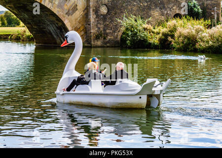 People enjoying a relaxing trip on a swan shaped pedalo boat on the River Thames at Lechlade-on-Thames, on the edge of the Cotswolds. Gloucestershire, UK. - Stock Image