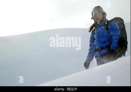 A woman walking in a snowstorm - Stock Image