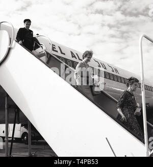 1960s, historical, an air stewardess waits at the bottom of the steps to see passengers depart from an El Al aircraft at Heathrow Airport, London, England, UK. - Stock Image