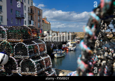 Lobster traps and working fisherman with fishing boats moored at St Andrews Pier Kinness Burn St Andrews Fife Scotland UK - Stock Image