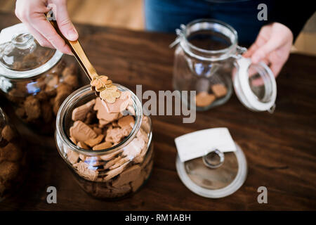 A midsection of a customer buying biscuits in zero waste shop. A top view. - Stock Image