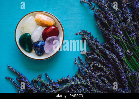 Rainbow Stones with Lavender on Turquoise Table - Stock Image