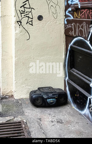 Old technology - Abandoned, dumped, trashed. Redundant radio & CD player dumped on a city pavement. - Stock Image