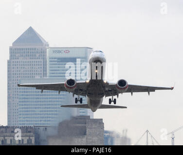 Baboo Embraer 190 climbing out after take-off with Canary Wharf behind - Stock Image